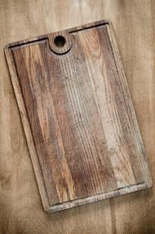 Placa de corte de madeira rústica no fundo de madeira.