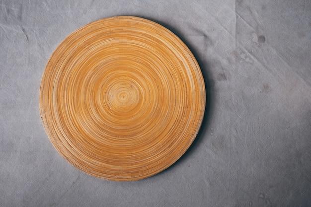 Placa de corte de madeira vazia na tabela com toalha de mesa cinzenta com fundo da mancha.
