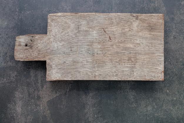 Placa de corte de madeira vintage vazia configurada em fundo escuro de concreto com espaço de cópia.