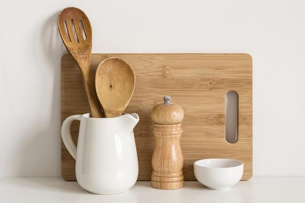 Placa de corte de utensílios de cozinha, colheres e moinho de especiarias no fundo da parede da mesa.