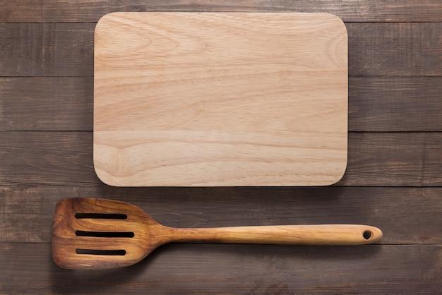Placa de corte e espátula no fundo de madeira