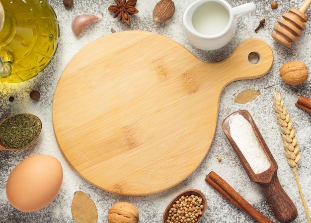 Placa de corte e ingredientes de padaria em fundo de madeira