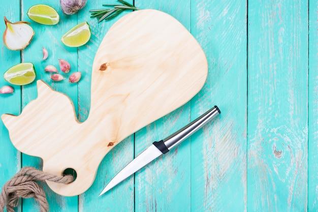 Placa de corte em forma de gato com uma faca em uma mesa de madeira vintage