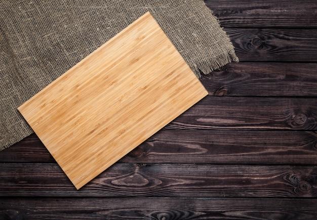 Placa de corte na mesa de madeira velha escura. vista do topo