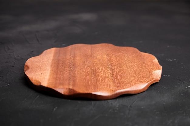 Placa de corte na mesa de pedra preta. tábua de cortar de madeira redonda vazia em fundo escuro