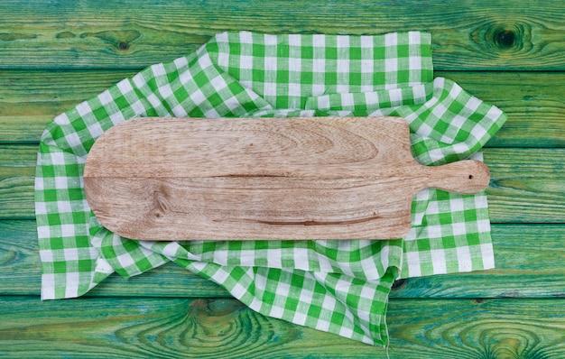 Placa de corte na toalha de mesa quadriculada verde