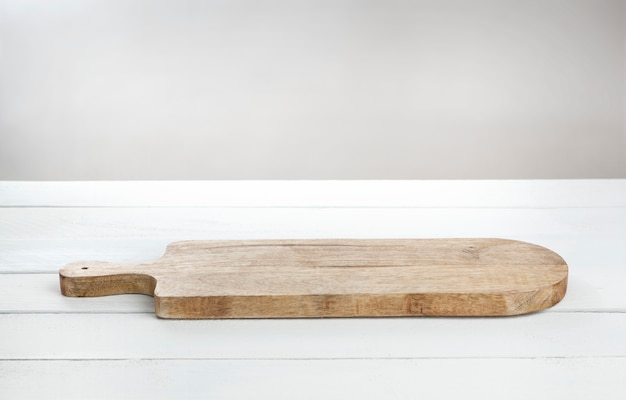 Placa de corte para queijo na mesa de madeira branca.