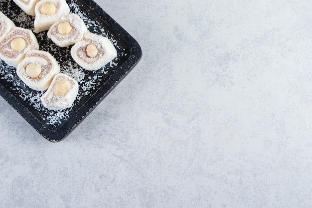 Placa de corte preta de deliciosas guloseimas com nozes na pedra.
