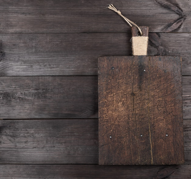 Placa de corte quadrada marrom muito antiga com uma alça