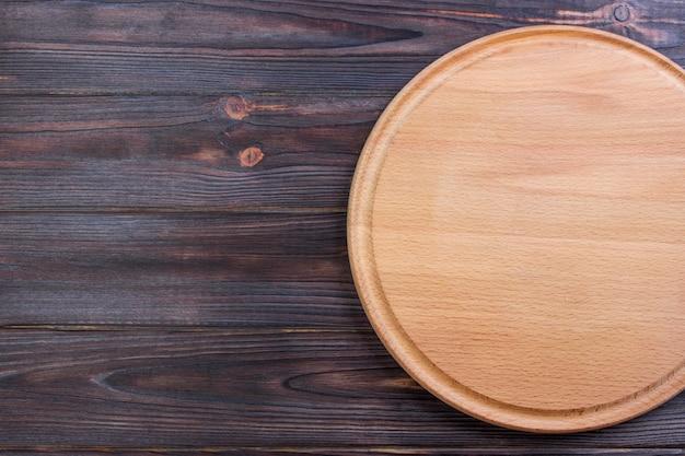 Placa de corte redondo no fundo de textura de madeira velha