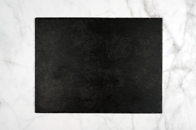Placa de corte retangular de ardósia preta, tabuleta vazia no mármore claro.