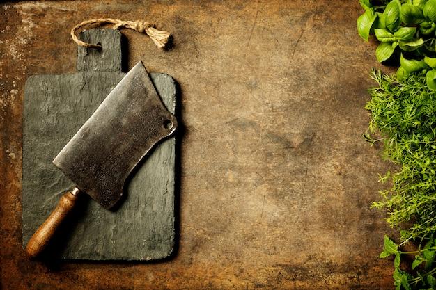 Placa de corte vintage, cutelo e ingredientes de cozinha