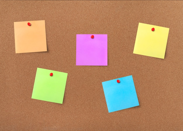 Placa de cortiça com notas em branco coloridas com traçado de recorte