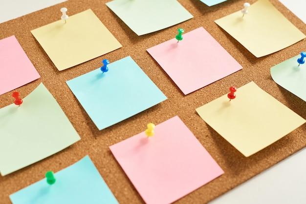 Placa de cortiça com notas em branco coloridas fixadas