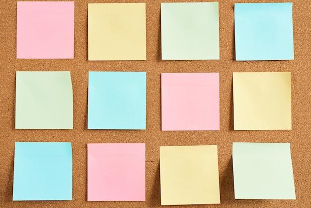 Placa de cortiça com notas em branco de papel colorido, close-up