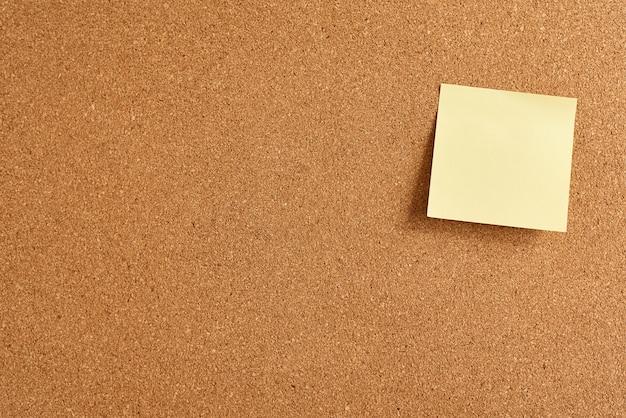 Placa de cortiça com uma nota em branco de papel amarelo