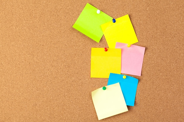Placa de cortiça com várias notas em branco coloridas com pinos