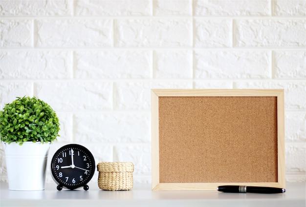 Placa de cortiça em branco simulado acima com relógio, plantas verdes na parede de tijolo branco
