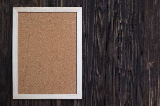 Placa de cortiça vazia com moldura de madeira na mesa de madeira