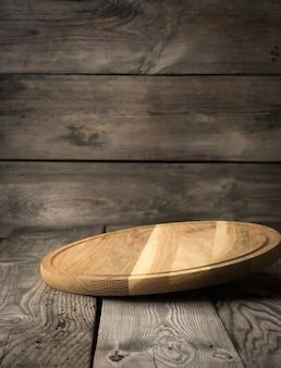 Placa de cozinha de corte de madeira redonda vazia na mesa de madeira, tabuleiro de pizza