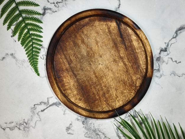 Placa de cozinha de madeira sobre uma mesa de mármore. faça uma simulação para a apresentação do produto. vista de cima.