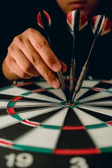 Placa de dardo de seta vermelha com mão segure o conceito de estratégia de negócios closeup apontar para o objetivo