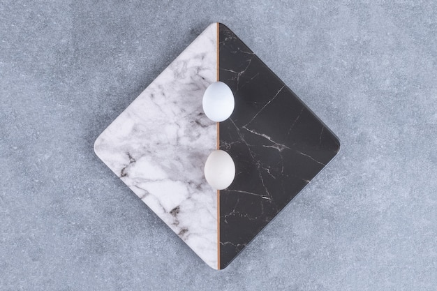 Placa de duas cores de ovos frescos crus na pedra.