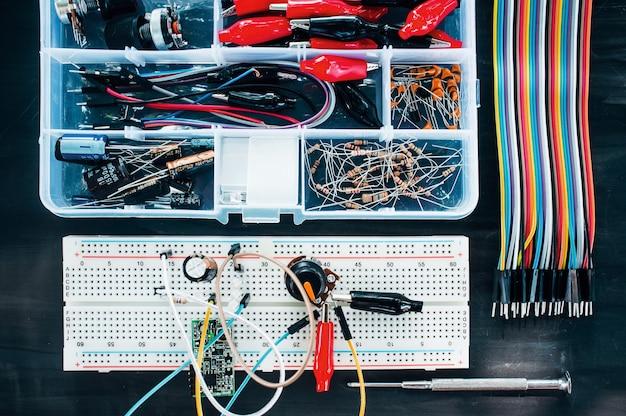 Placa de ensaio com elementos, cabos coloridos e caixa de ferramentas