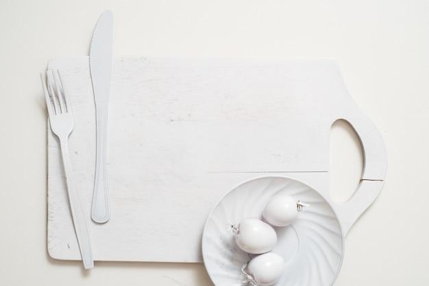 Placa de faca garfo branco em uma bandeja de prancha de madeira velha