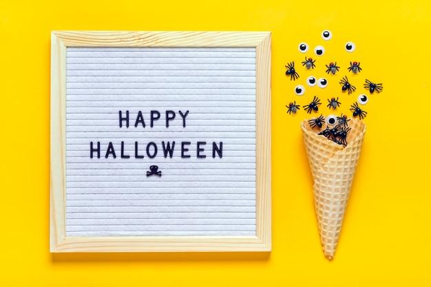 Placa de feltro com texto, citação, aranhas pretas e moscas, olhos arregalados rastejam para fora da casquinha de sorvete. vista superior flat lay feliz halloween conceito criativo cartão de férias.