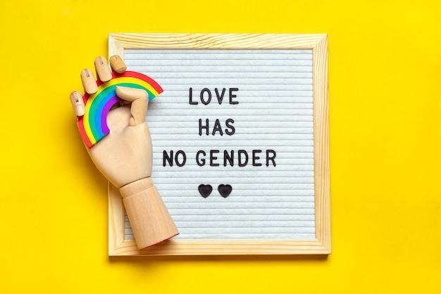 Placa de feltro, mão de madeira segura arco-íris com cores de lgbt isoladas em amarelo