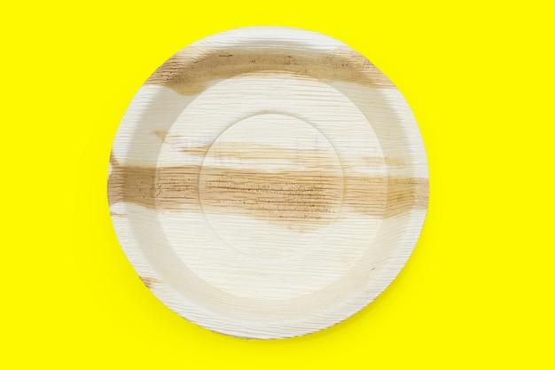 Placa de folha de palmeira de bétele em fundo amarelo.