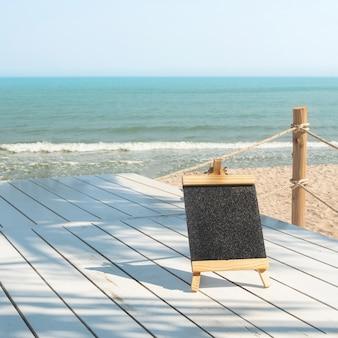 Placa de giz com moldura de madeira com fundo de areia da praia