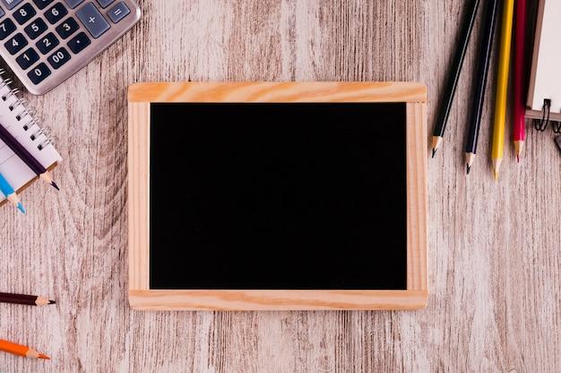 Placa de giz e papelaria na superfície de madeira