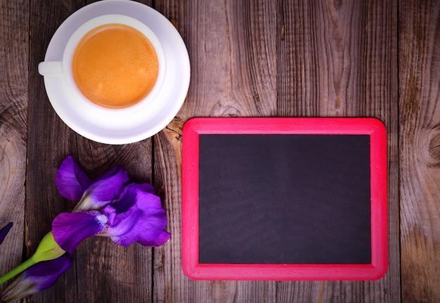 Placa de giz preto vazio com uma xícara de café sobre uma superfície cinza