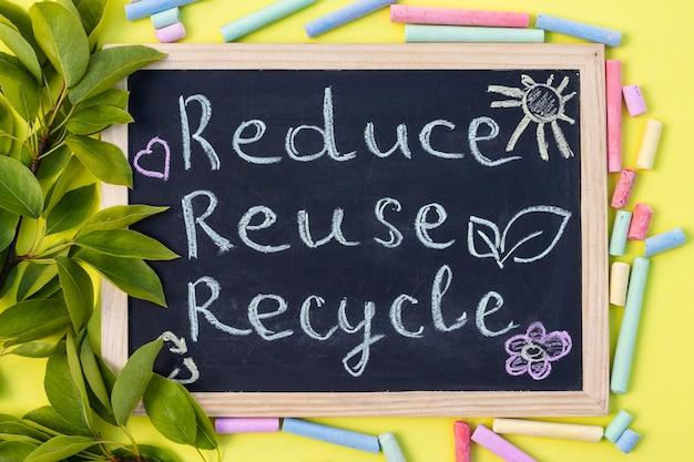 Placa de giz reduse reuse recycle cadastre-se em um fundo amarelo com folhas verdes e pedaços de giz. vista do topo.