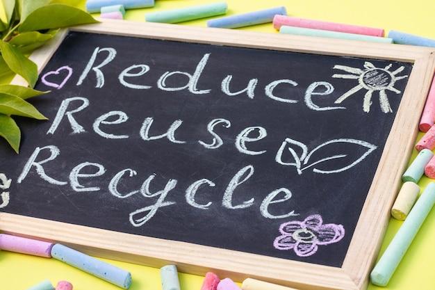 Placa de giz reduse reuse recycle cadastre-se em um fundo amarelo com folhas verdes e pedaços de giz.