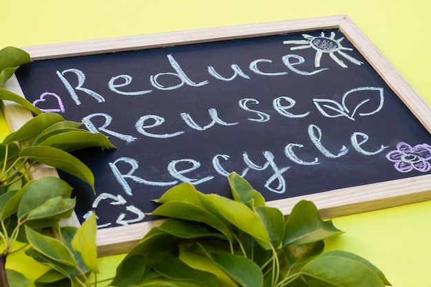 Placa de giz reduse reuse recycle cadastre-se em um fundo amarelo com folhas verdes.