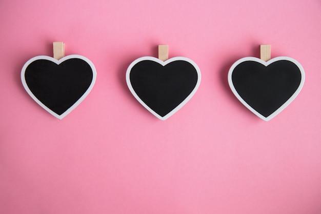 Placa de giz três para anotações em forma de coração no fundo rosa