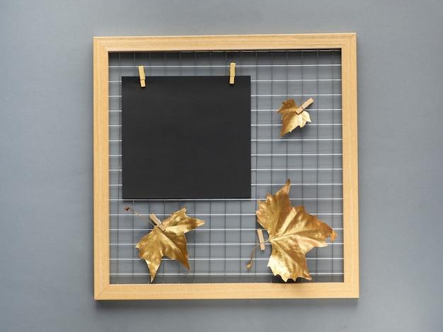 Placa de grade de foto com folhas de outono douradas e maquete de papel preto para sua arte de letras ou caligrafia