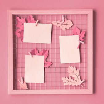 Placa de grade de foto com folhas de papel de outono e cartões de papel em branco em estacas. maquete na moda monocromática rosa para suas fotos ou escrita, composição de quadrados.