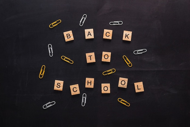 Placa de grafite preta com a inscrição de letras de madeira de volta às aulas perto da cor do papel de carta ...