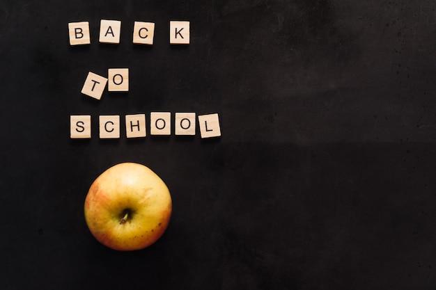 Placa de grafite preta com letras de madeira de volta às aulas e um espaço de cópia de maçã amarela madura