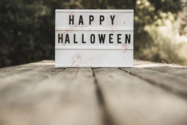 Placa de halloween colocada na mesa de madeira