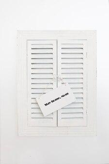 Placa de identificação com palavras fique em casa, mãe na janela de venezianas de madeira. conceito de quarentena em casa como medida preventiva contra o surto de vírus corona covid 19.
