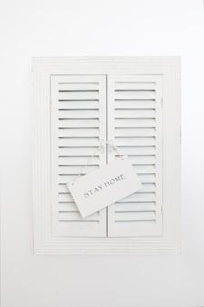 Placa de identificação com palavras fique em casa na janela de venezianas de madeira. conceito de quarentena em casa como medida preventiva contra o surto de vírus corona covid 19.