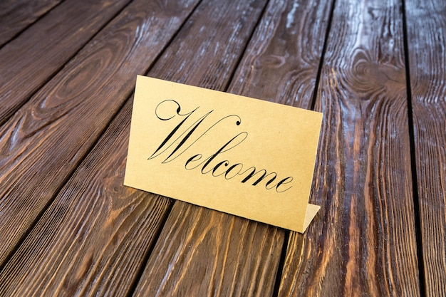 Placa de identificação de papel, palavra de boas-vindas na velha mesa de madeira