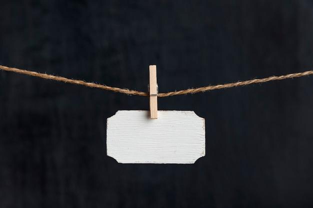 Placa de identificação pequena. placa de madeira em branco pendurar com prendedores de roupa na corda em fundo preto. copie o espaço.