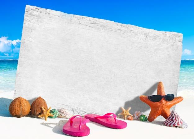 Placa de madeira branca com outros objetos pela praia