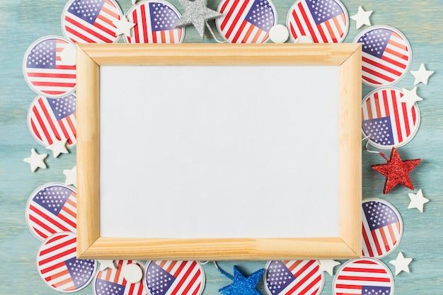 Placa de madeira branca sobre os emblemas de bandeira do eua e estrelas no pano de fundo texturizado azul